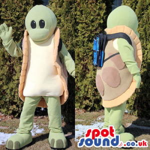 Funny green turtle mascot with a blue rucksack on the back -