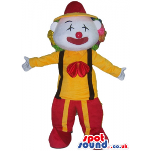 Clown with multicolored hair and a red nowse wearing a yellow