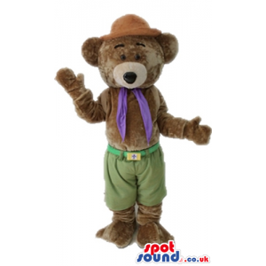 Brown bear wearing a brown hat, green trousers and a purple