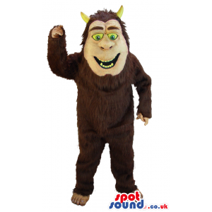 Brown Ogre Mascot With Yellow Teeth And Horns And Green Eyes -