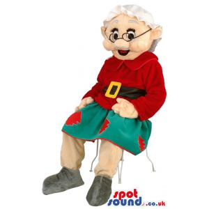 Grandmother mascot is sitting in a chair red and green clothes