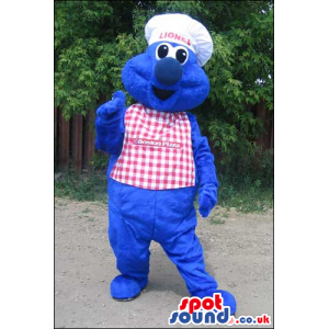 Blue Monster Mascot Wearing A Checked Apron And A Chef Hat -