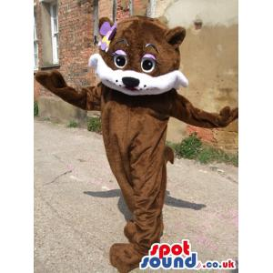 Brown bear mascot standing with a purple flower in her head -