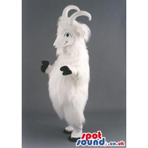 White furry goat mascot with two horns standing and smiling -