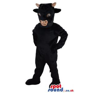 Black cow mascot standing and keeping his hands on waist -