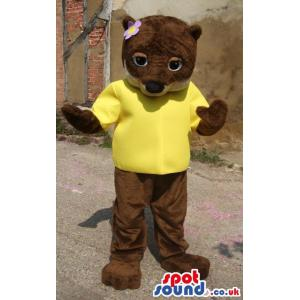 Brown girly bear mascot with a t-shirt and a flower on her head