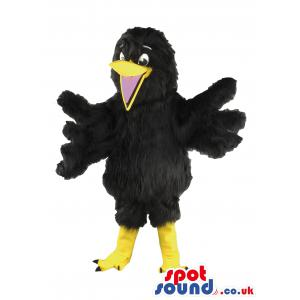 Black crow mascot with his wings wide open and an open mouth -