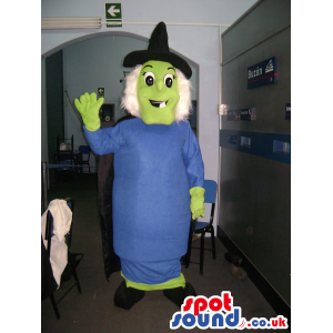 Green witch mascot with blue dress, black pointy hat and cape -