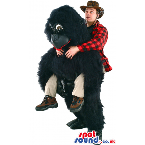 Giant black gorilla mascot with dark eyes and red tongue -