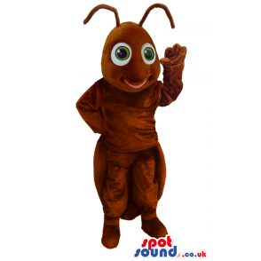 Standing brown, smiling ant mascot with wide round green eyes -