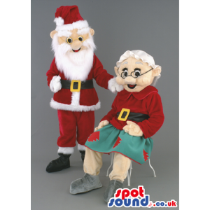 Mr and Mrs Claus mascot in traditional red santa outfil -
