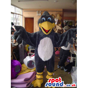 Large cheerful grey eagle mascot with green eyes and yellow