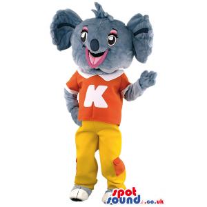Tall overjoyed Koala mascot wearing orange T-shirt with K