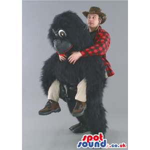 Tall fluffy black gorilla mascot with red lips and brown eyes -