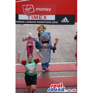 Blue and grey shark mascot holding a bloodied human leg -