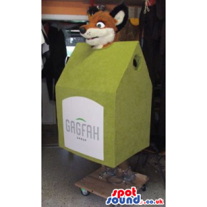 Brown Fox Plush Mascot Inside A Green House With A Label -