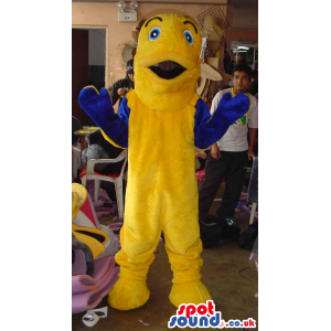 Giant yellow fish mascot with blue hands and yellow feet -
